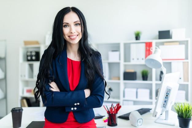 Linda garota em um terno de negócio está de pé no escritório, inclinando-se sobre uma mesa