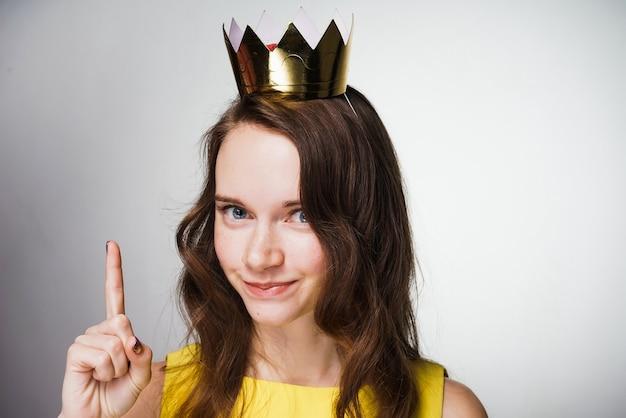Linda garota em um vestido amarelo levantou o dedo, uma ideia apareceu em sua cabeça, uma coroa de ouro