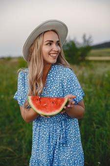Linda garota em um vestido azul e um chapéu. mulher em um campo de verão. menina com uma melancia.