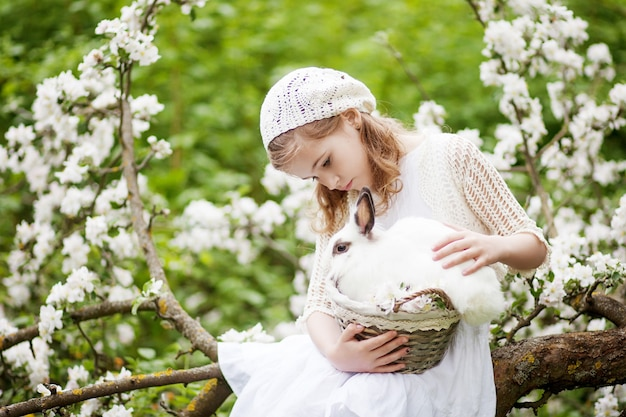 Linda garota em um vestido branco, brincando com um coelho branco no jardim de flores de primavera. atividade divertida de primavera para as crianças. tempo da páscoa