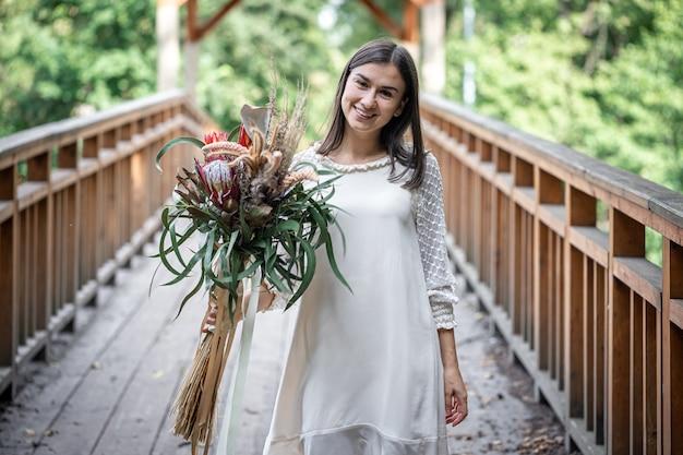Linda garota em um vestido branco com um buquê de flores exóticas em uma ponte de madeira.