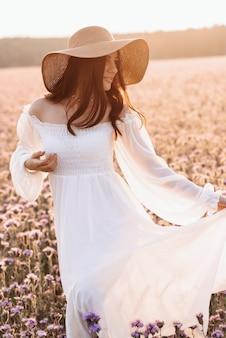 Linda garota em um vestido branco em um campo de lavanda ao pôr do sol.