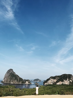 Linda garota em um vestido branco observando as ilhas tropicais verde-escuras exóticas com pedras, mar azul e céu azul claro no parque nacional ao phang-nga