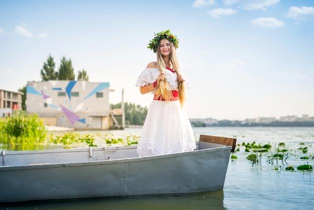 Linda garota em um vestido nacional em um barco no lago