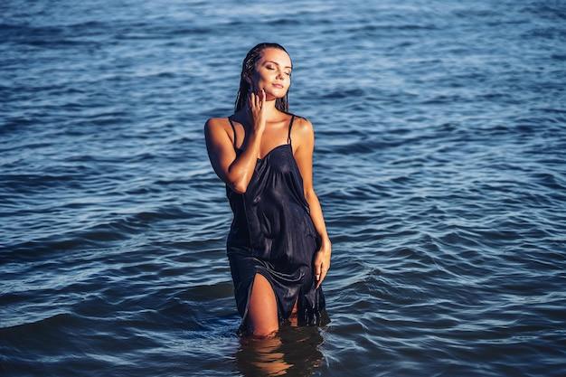 Linda garota em um vestido posando em água tropical ilha linda rosto bronzeado cuidados com a pele