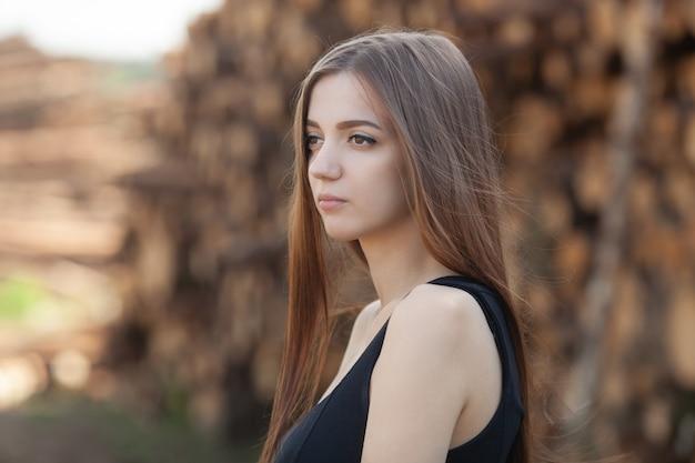 Linda garota em um vestido preto em pé ao ar livre, perto da floresta