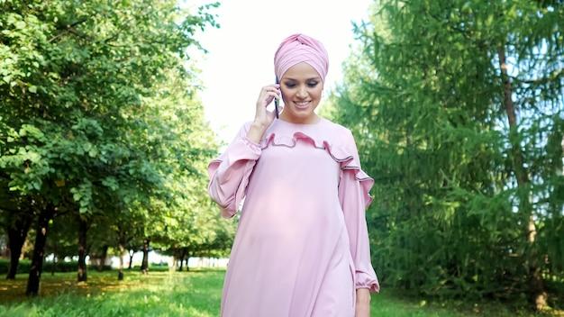 Linda garota em um vestido roxo com palestras de hijab em um smartphone preto vagando pelo parque verde sob o sol forte de verão