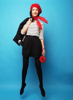 Linda garota em uma boina vermelha. estilo francês. sobre fundo azul.