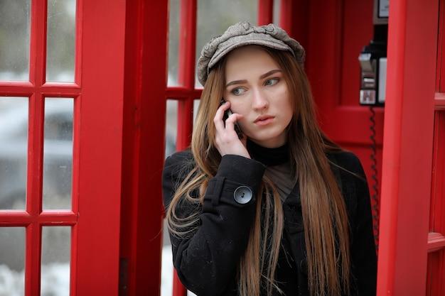 Linda garota em uma cabine telefônica. a garota está falando ao telefone do telefone público. cabine telefônica inglesa na rua e uma mulher falando ao telefone.