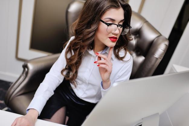 Linda garota em uma camisa branca está sentado no monitor do computador.