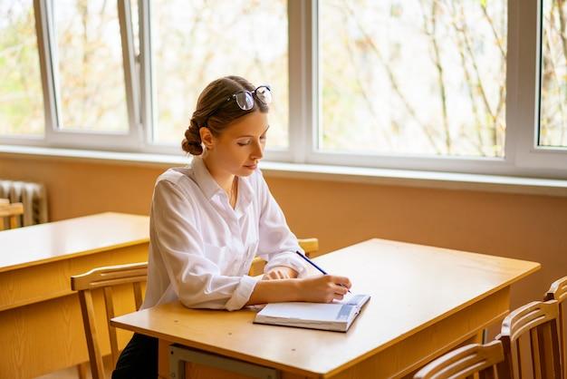 Linda garota em uma camisa branca, sentado à mesa pela janela na sala de aula, lendo um livro