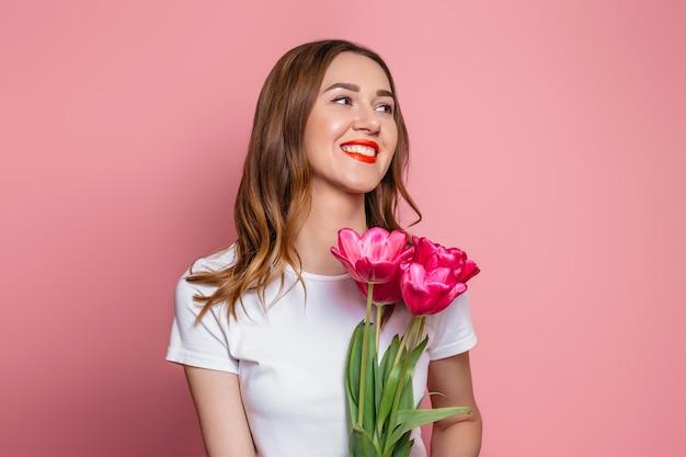 Linda garota em uma camiseta branca detém um buquê de tulipas isoladas em um fundo rosa
