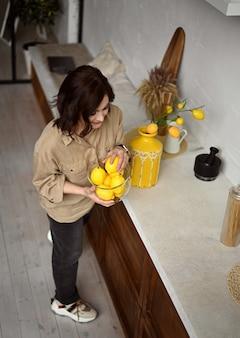 Linda garota em uma cozinha bege com limões amarelos estilo siciliano itália