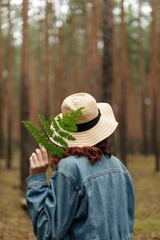 Linda garota em uma floresta de pinheiros. uma garota segura uma samambaia. uma garota de chapéu caminha pela floresta. atmosfera da floresta