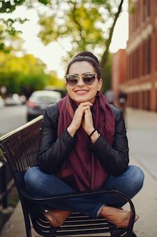 Linda garota em uma jaqueta de couro e cachecol sentado nas ruas de Chicago