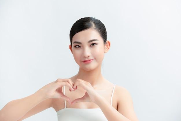 Linda garota em uma parede branca fez um coração com as mãos perto do peito