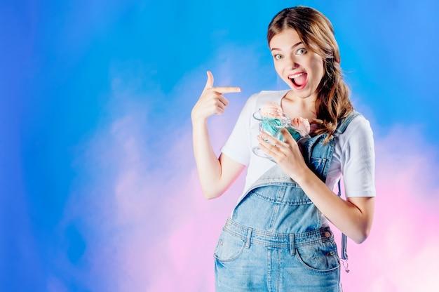 Linda garota emocional aponta um dedo para si mesma, sobre um fundo azul com um delicioso sorvete rosa nas mãos. conceito de venda doce, venda