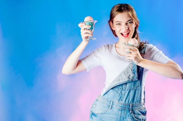 Linda garota emocional em um azul tem nas mãos um delicioso sorvete rosa. venda doce, venda