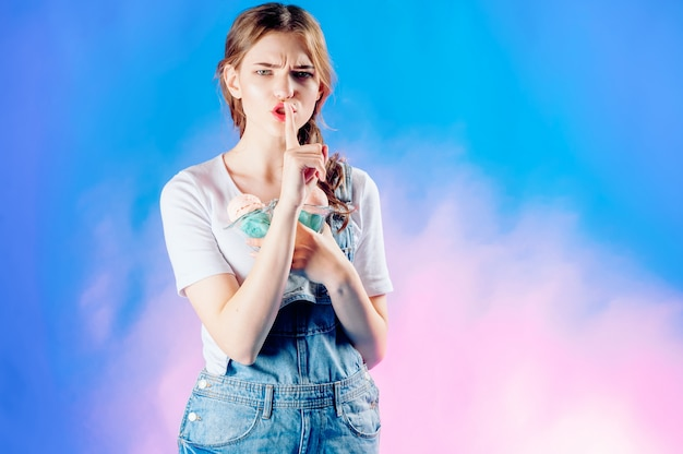 Linda garota emocional sobre um fundo azul tem nas mãos um delicioso sorvete rosa. conceito de venda doce, venda