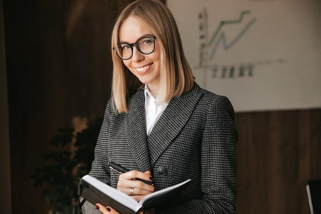 Linda garota empresária sorrindo alegremente enquanto segura um caderno e um retrato de caneta de um trabalhador de escritório
