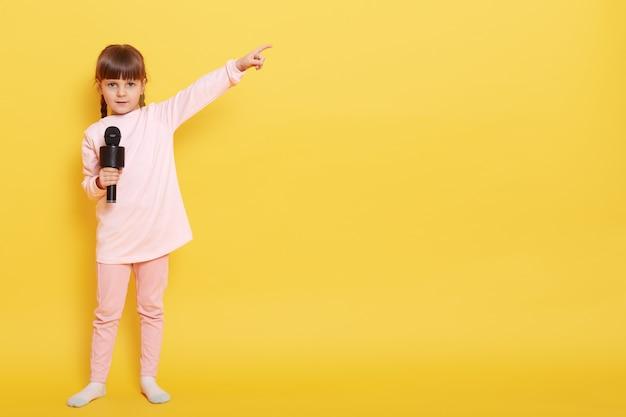 Linda garota encantadora cantando no microfone isolado sobre fundo amarelo, garoto vestindo roupas casuais rosa pálido, apontando de lado com o dedo indicador. copie o espaço para anúncio.