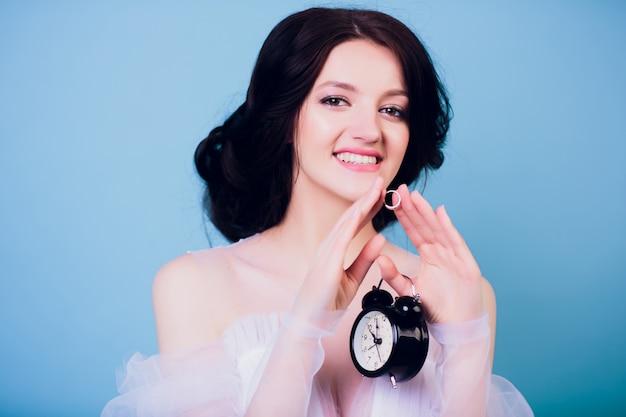 Linda garota encantadora no vestido de casamento branco, sendo tarde da manhã e segurando na mão retrô despertador e anel