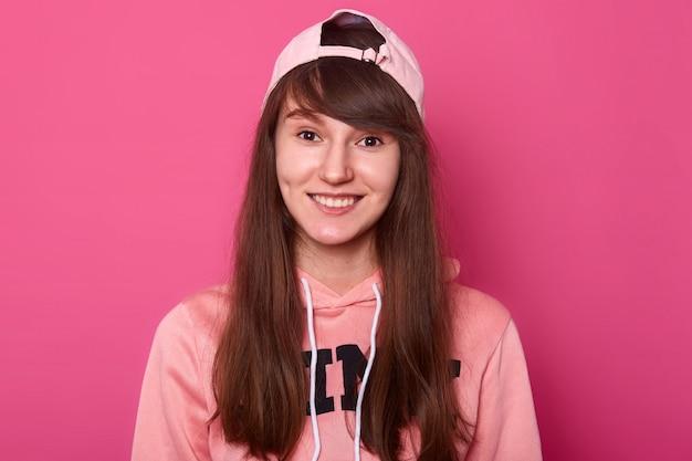 Linda garota encantadora usa capuz rosa e tampa de viseira de volta.