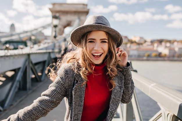 Linda garota encaracolada com elegante chapéu cinza posando na ponte em um dia ensolarado