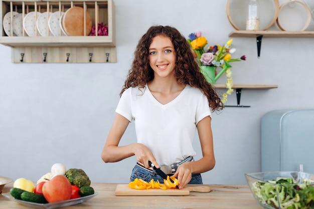 Linda garota encaracolada fatias de pimenta para salada na cozinha