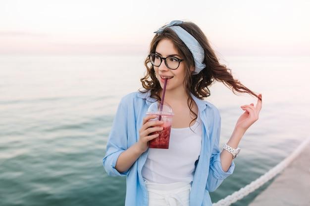 Linda garota encaracolada segurando suco de cereja e brincando com seus cabelos escuros durante uma caminhada ao longo do cais