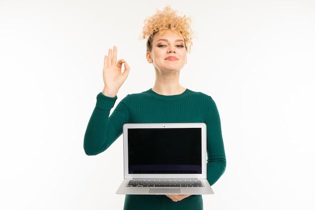 Linda garota encaracolada segurando um laptop com maquete nas mãos na parede branca