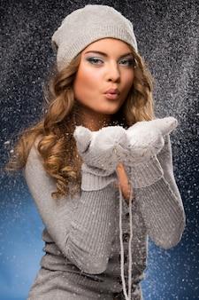Linda garota encaracolada usando luvas durante a queda de neve