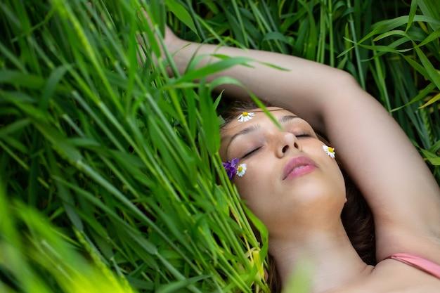 Linda garota encontra-se com os olhos fechados no campo de trigo verde com flores silvestres no rosto