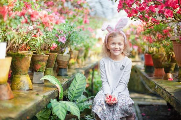 Linda garota engraçada com orelhas de coelho de páscoa no jardim. conceito de páscoa criança rindo na caça aos ovos de páscoa