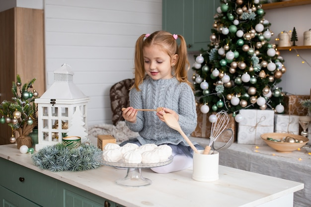 Linda garota engraçada está sentado na mesa da cozinha em casa de natal
