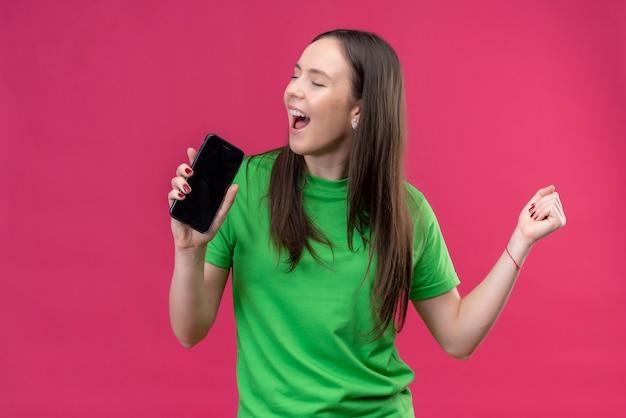 Linda garota engraçada vestindo uma camiseta verde segurando um smartphone e usando-o como microfone cantando em pé sobre o espaço rosa isolado