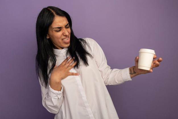 Linda garota enjoada de camiseta branca, segurando e olhando para uma xícara de café, colocando a mão no coração isolado no roxo