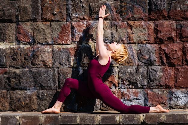 Linda garota envolvida em yoga no fundo de um muro de pedra