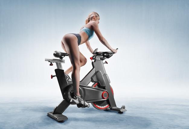 Linda garota esbelta e de pernas compridas se senta em uma bicicleta ergométrica. vista lateral.