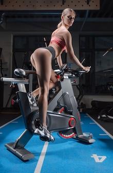 Linda garota esbelta e de pernas compridas se senta em uma bicicleta ergométrica. vista traseira.