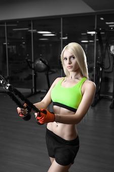Linda garota esbelta fazendo exercícios na academia
