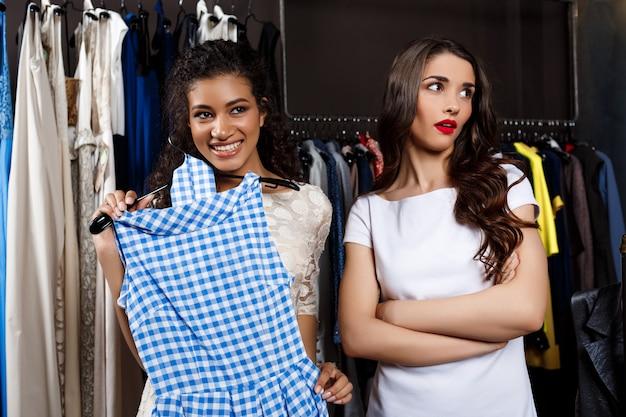 Linda garota, escolhendo o vestido no shopping.