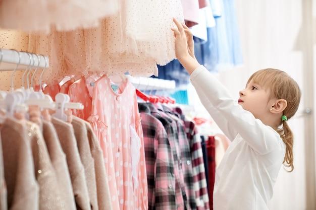 Linda garota, escolhendo roupas de crianças modernas e elegantes.