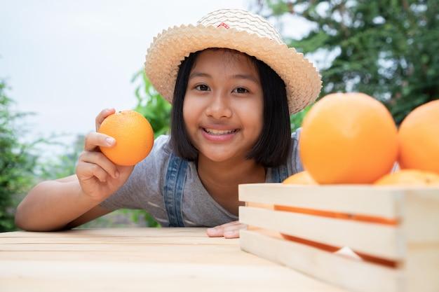 Linda garota escolhendo uma laranjas em caixa de madeira do jardim. ela gosta de jardinagem e venda de produtos. conceitos de agricultura e frutas não tóxicas.