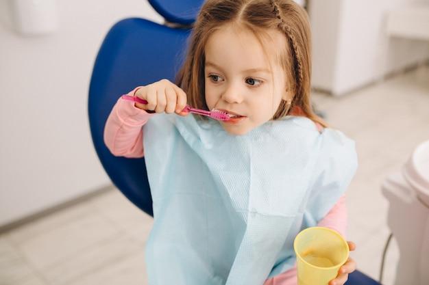 Linda garota escovando dentes odontologia