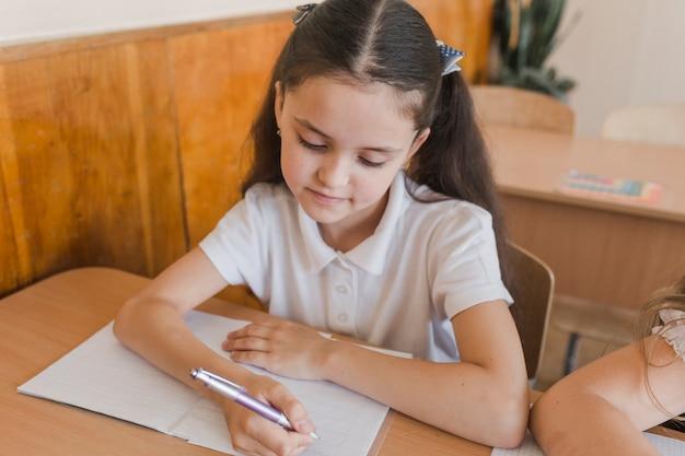 Linda garota escrevendo no caderno durante a lição