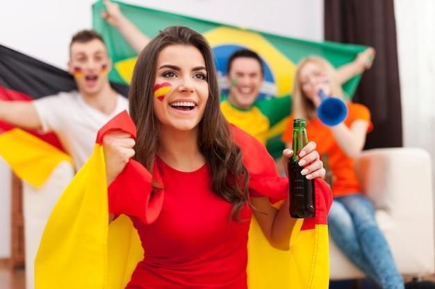 Linda garota espanhola com as amigas torcendo por uma partida de futebol
