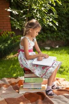 Linda garota esperta lendo um grande livro no parque em um dia de sol
