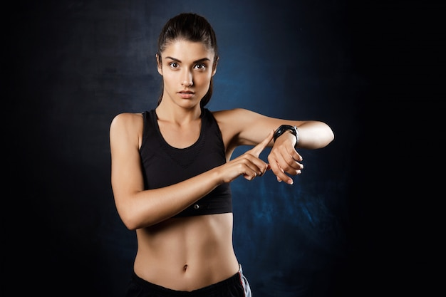 Linda garota esportiva, apontando para o relógio sobre parede escura.