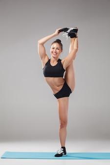 Linda garota esportiva em pose de acrobata ou asana de ioga
